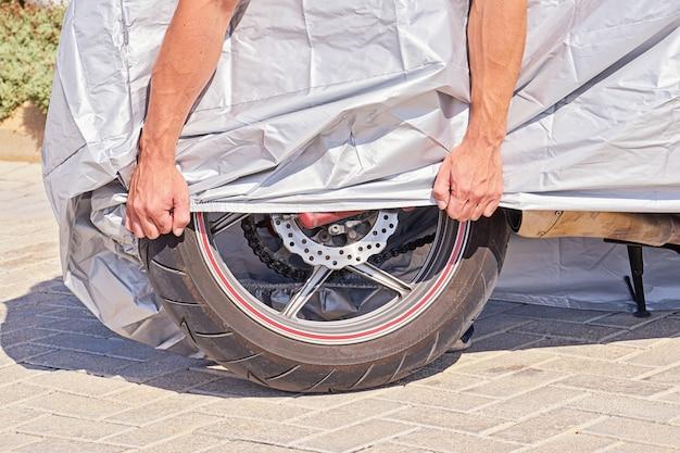 雨や過熱から保護するための布製シールドで覆われた駐車中の屋外バイク