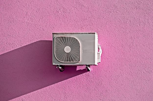 影とグランジピンクの壁にモダンなエアコンコンプレッサー