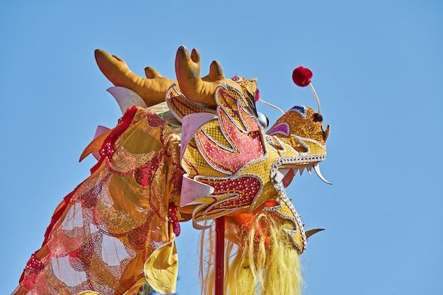 Голова китайского дракона против голубого неба во время празднования китайского нового года