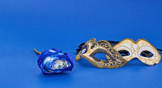 コピースペースと青色の背景にマルディグラのカーニバルの仮面舞踏会マスク