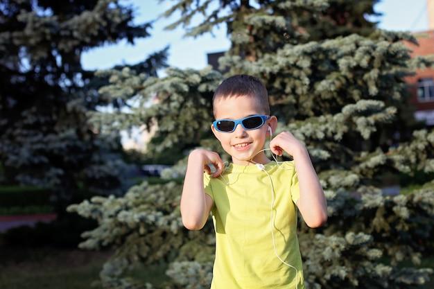 Мальчик слушает музыку в наушниках и танцует
