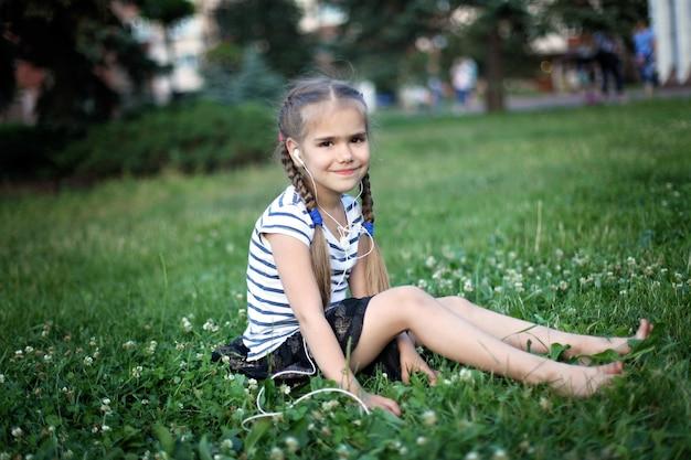 緑の芝生に座って音楽を聴くかわいい女の子