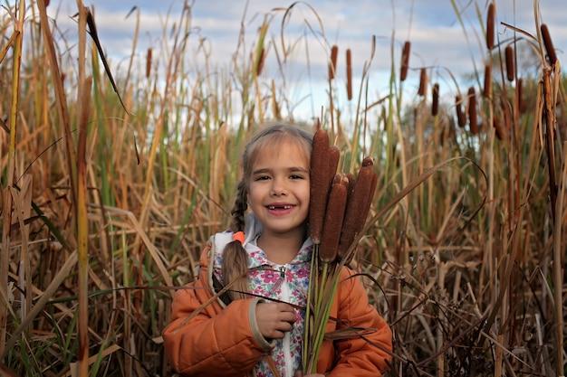 Счастливые дети веселятся в области рогоз, концепция экологии