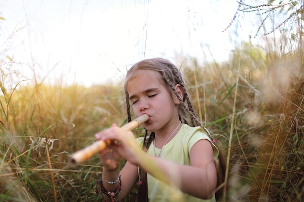 Девушка играет на флейте в поле