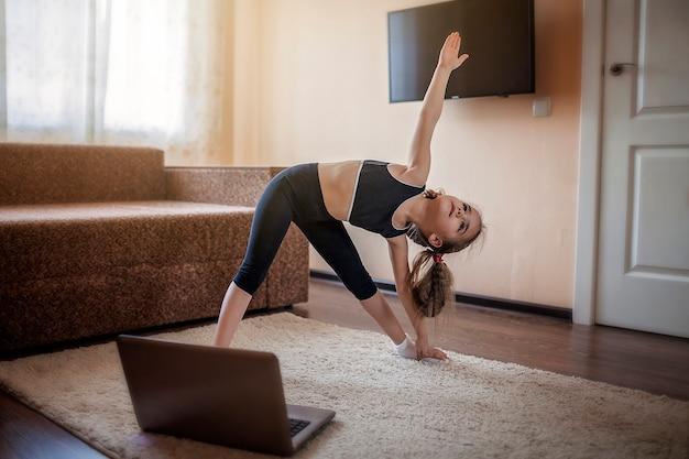 Хорошенькая молодая девушка в спортивной одежде смотрит онлайн-видео на ноутбуке и занимается фитнесом дома