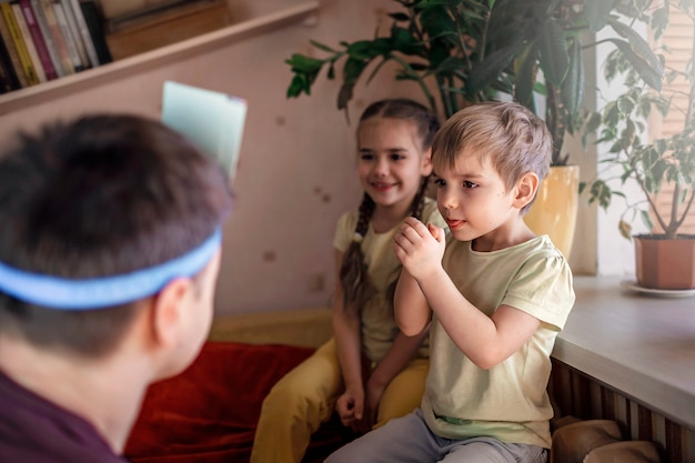 Счастливый взрослый отец играет в настольную игру со своими двумя детьми в домашнем интерьере, семейные ценности на самом деле