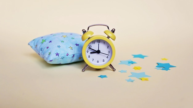 黄色の目覚まし時計と水色の枕