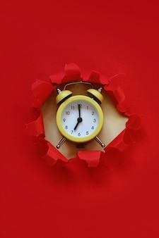 Желтый будильник из отверстия бумаги