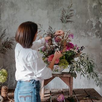 女性のプロの花屋が野生の花のアレンジを準備します。
