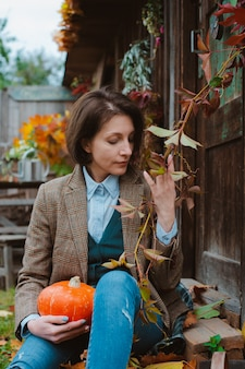 茶色の暖かいジャケットと素朴な背景にジーンズの若い女性。