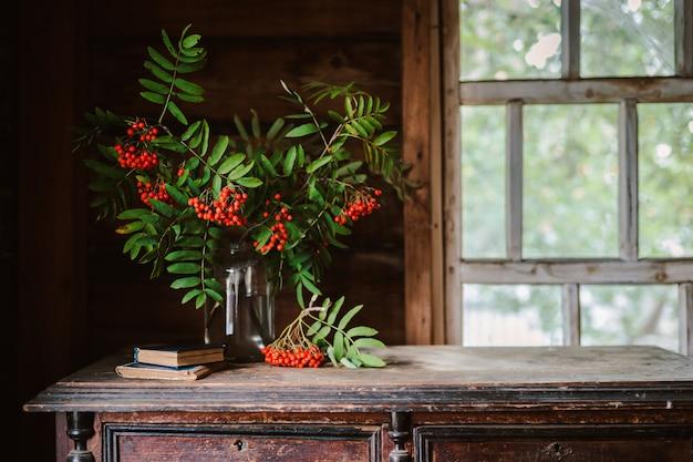 Ветвь рябины на фоне деревенского деревянного мокрого окна