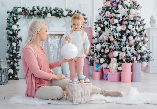 Мама и дочка украсили елку розовым в помещении