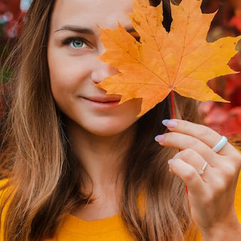 黄色の秋の葉で彼女の顔を覆っている美しい若い女性