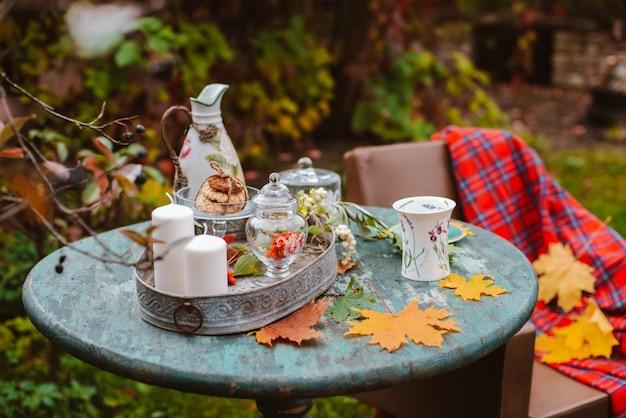 居心地の良いパティオ。秋の葉は食器カップクッキーと木製アンティークラウンドテーブルにあります。