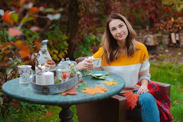若い女性がテーブルに座っている赤毛に対して毛布オープンエアで秋の快適な椅子
