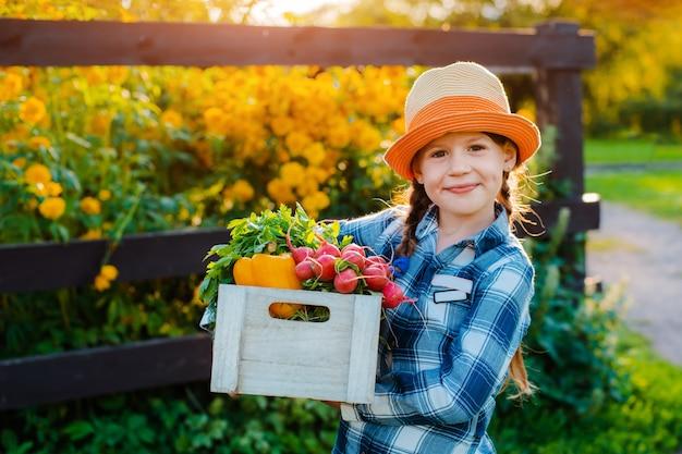 Маленькая девочка держит корзину со свежими органическими овощами