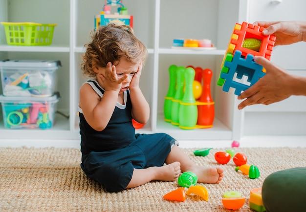 教育的なプラスチックのおもちゃで部屋の床で遊ぶ赤ちゃん