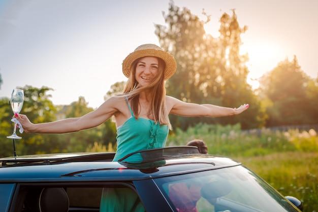 陽気な女の子の女性は、自然の中で夏のパーティーで車のハッチから傾いているワインのグラスと喜んでいます。