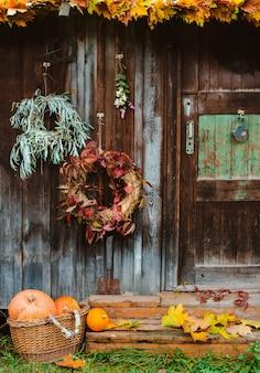 秋のフロントポーチ。秋の花輪と古い木製の素朴なカボチャ