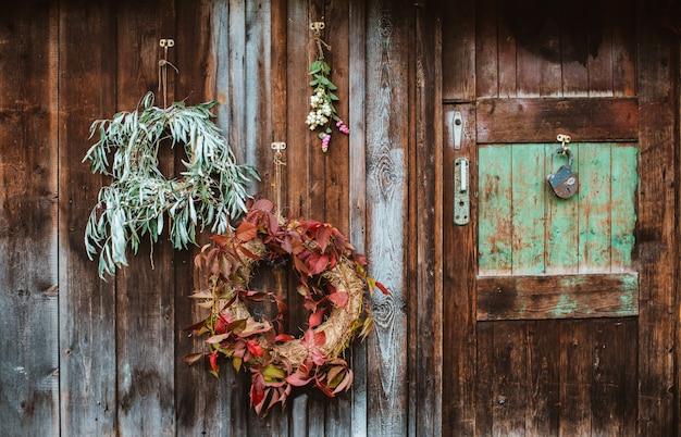 秋のフロントポーチ。秋の花輪と古い木製の素朴な壁にカボチャ