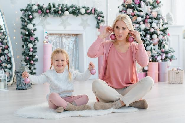 ママと娘は、クリスマスツリーの休日の準備を楽しんでいます