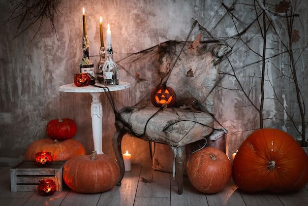 ハロウィーンのお祝いの装飾。ジャックのカボチャと燃えるろうそく、クモの巣、魔女のほうきがコンクリートの壁にある恐ろしい構成