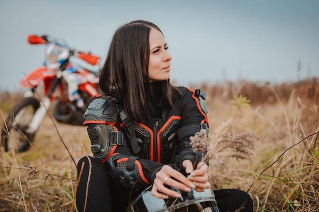 Красивая брюнетка женщина в мотоцикл наряд. женский мотокросс гонщик рядом с ее мотоциклом