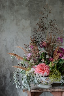 コンクリートの壁の背景にデスクトップの花屋で大規模なフラワーアレンジメントブーケ