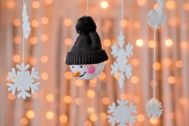 Снеговик и снежинки висят как елочные украшения