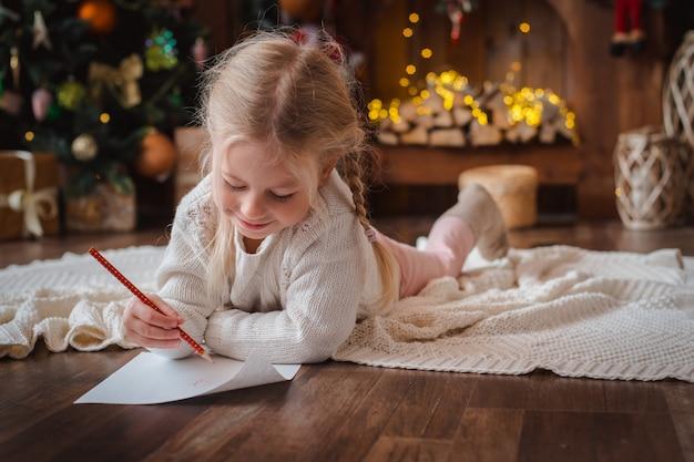 Маленькая детская девочка пишет письмо деду морозу и мечтает о подарке