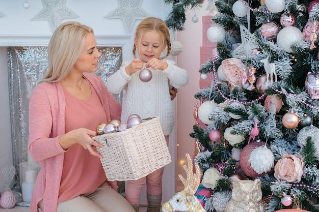 Мама и дочь украшают елку в помещении.
