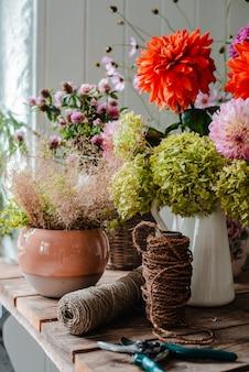 Большой букет из цветочных композиций на рабочий стол флориста на фоне бетонной стены