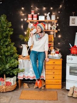 Женщина яркая шляпа кухонная плита. девушка готовит зимний вечер. деревянная деревенская кухня на черном фоне.