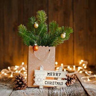 クリスマスの組成物。茶色の木製の背景とボケライトにモミの枝と紙袋。