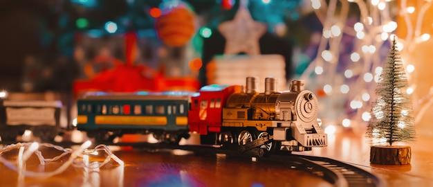 装飾クリスマスツリーの下の床におもちゃのヴィンテージ蒸気機関車
