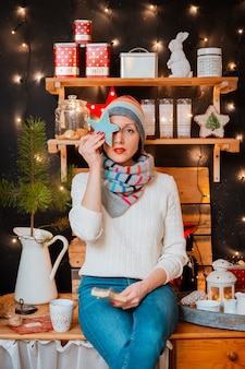 Женщина яркая шляпа кухонная плита. девушка готовит зимний вечер. деревянная деревенская кухня