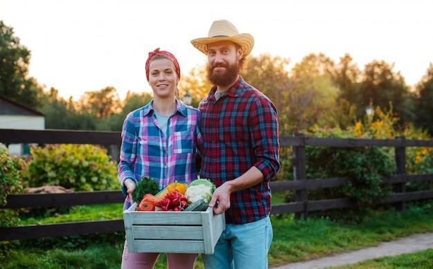 Мужчина и женщина держат коробку с урожаем сельскохозяйственных овощей