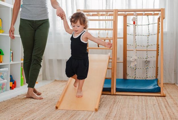 Ребенок занимается на дому детским деревянным спортивным комплексом.