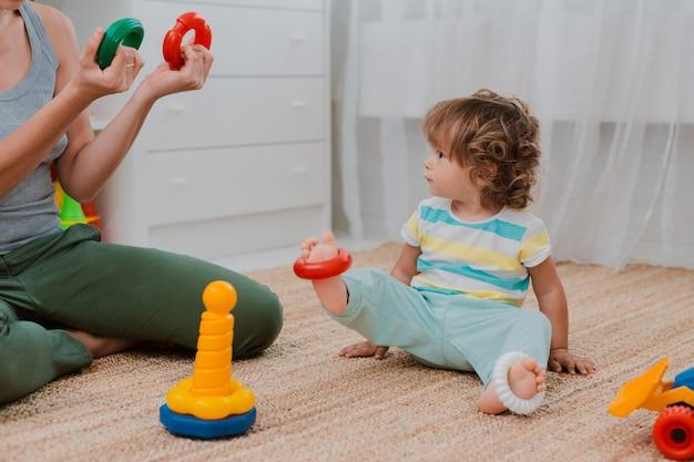 母と子は保育園の床で遊ぶ。ママと小さな男の子はプラスチック製のカラフルなおもちゃでやっています。