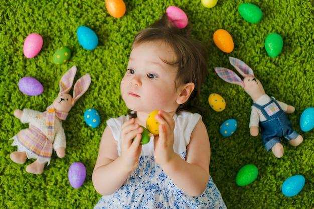 Ребенок лежит на траве с пасхальными яйцами и зайцем