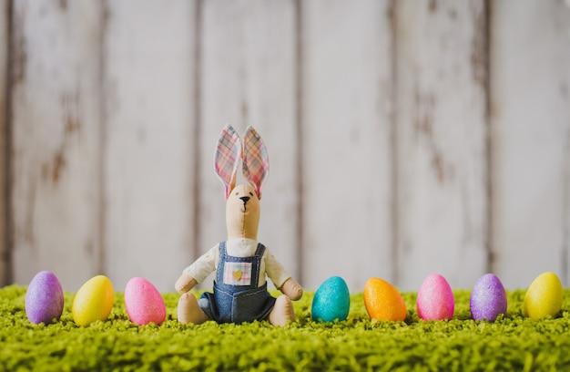Заяц сидит на траве с пасхальными яйцами