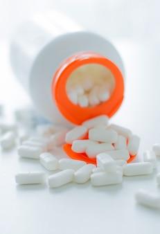 Белые таблетки, разлив из пластиковой белой бутылки с таблеткой