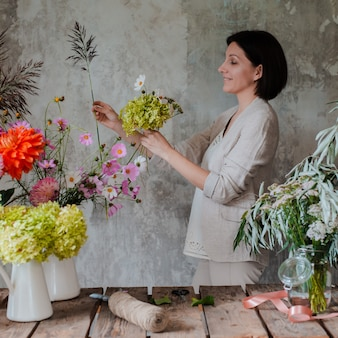 Женский профессиональный флорист готовит композицию из полевых цветов.