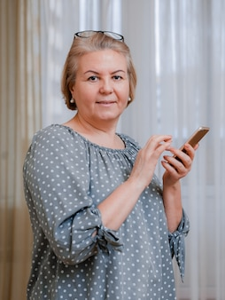 Привлекательная пожилая деловая женщина с мобильным телефоном улыбается, глядя на экран по видеосвязи