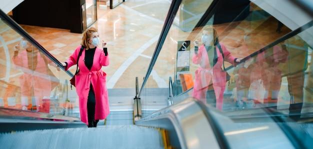 Красивая женщина в розовом надевает медицинскую маску для защиты от коронавируса, боясь заражения, поднимается на эскалаторе в торговом центре.