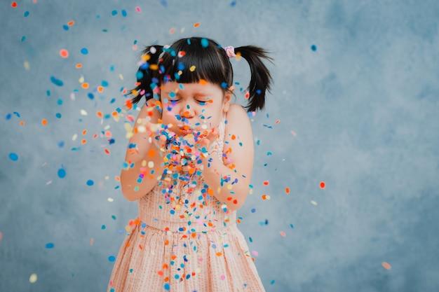 小さな女児は元気にカラフルな見掛け倒しと紙吹雪をスローします。