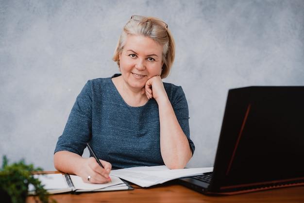 彼女の机でラップトップを持つ美しい作業深刻なビジネス高齢者の女性の肖像画