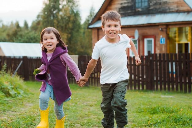 村の家を手で走る兄妹。私の祖母との村での休暇。