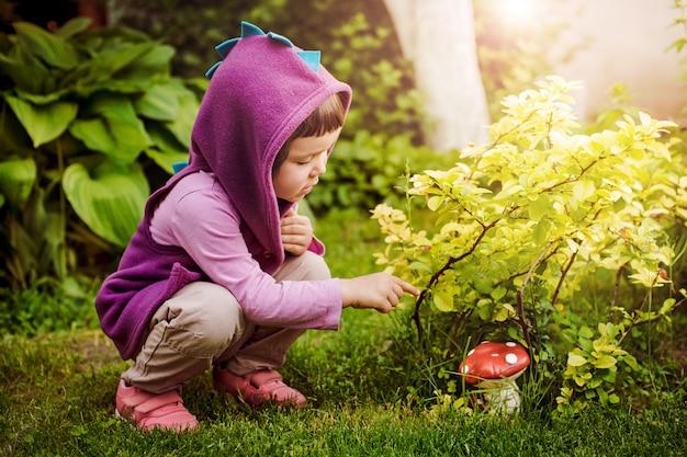 かわいい女の子が非食用の毒キノコを見て夏の森でキノコを選ぶ