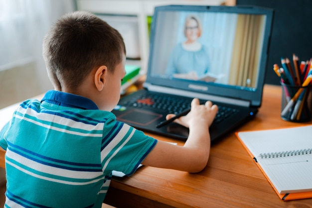 オンライン教育の遠隔学習。男子生徒は家で勉強し、宿題をします。家庭用遠隔学習